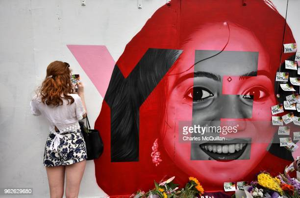 A woman writes a note on the Savita Halappanavar mural as the results in the Irish referendum on the 8th amendment concerning the country's abortion...