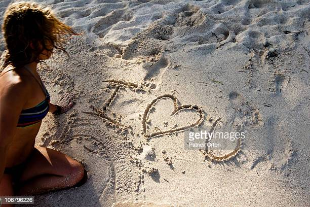 Woman writes I love you on the beach in Mexico.