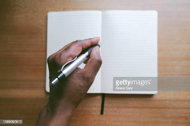 woman writes in notebook - 左利き ストックフォトと画像