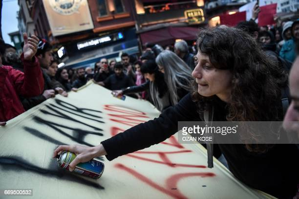 """Woman writes """"No"""" with a spray on a banner as she takes part in a gather of """"No"""" supporters, at the Besiktas district, in Istanbul, on April 17, 2017..."""
