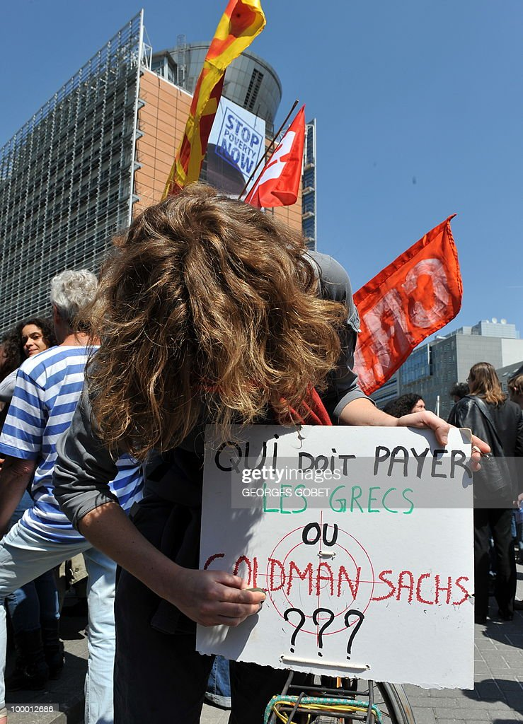 A woman writes on a placard reading 'Who Must Pay, The Greek People or Goldman Sachs ??' during a demonstration in solidarity with the Greek workers in front of the EU Commission bulding on May 20, 2010 in Brussels. Meanwhile, more than 20,000 Greeks took to the streets of Athens and second city Thessaloniki on Thursday in a new general strike against the government's debt-dictated austerity spending cuts and pension reform.