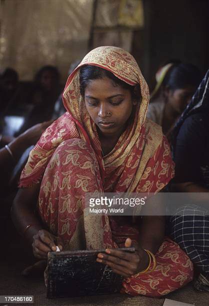 A woman writes on a slate in the class of an adult education program run by CONCERN in a village in Bangladesh The adult literacy rate in Bangladesh...