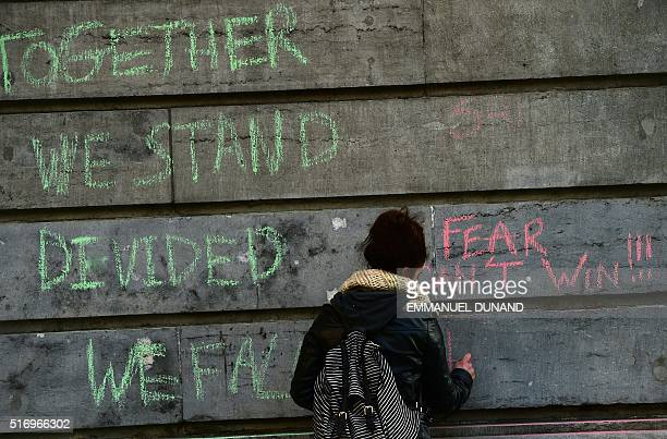 A woman writes on a wall reading messages Together we stand divided we fall and Fear can't win as she gather with other people in tribute to victims...
