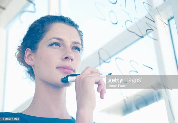 Woman writes on glass