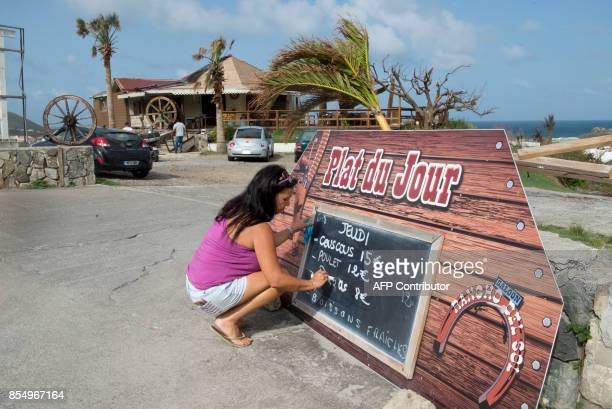 A woman writes the daily specials on a menu board out side the Rancho Del Sol restaurant in the northeastern area of the French Caribbean island of...