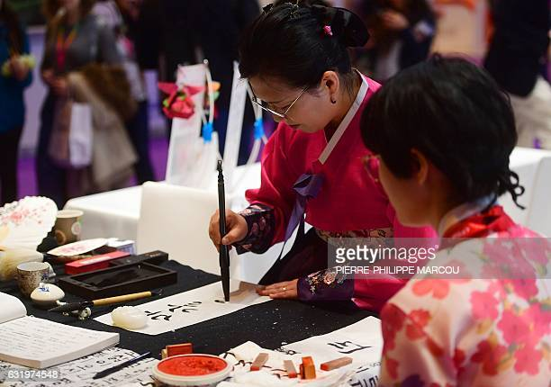 A woman writes the name of a visitor performing calligraphy at the Korean stand during the International Tourism Fair in Madrid on January 18 2017 /...