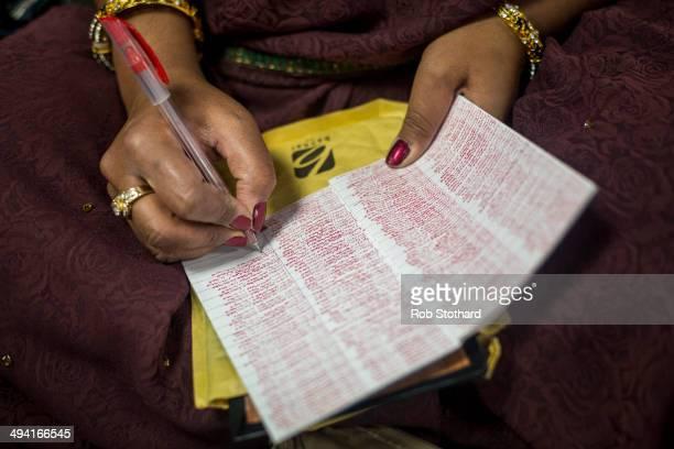 A woman writes the name of god Swaminarayanbapa Swamibapa at the Shree Swaminarayan Mandir a major new Hindu temple being built in Kingsbury before a...
