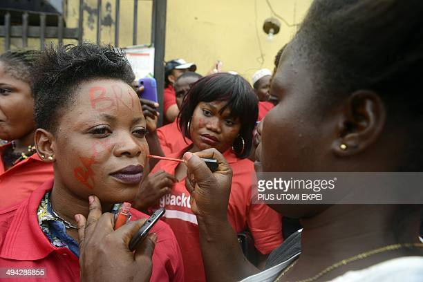 A woman writes the slogan 'Bring Back Our Girls' on the face of another as they prepare to march in Lagos on May 29 in a demonstration by civil...