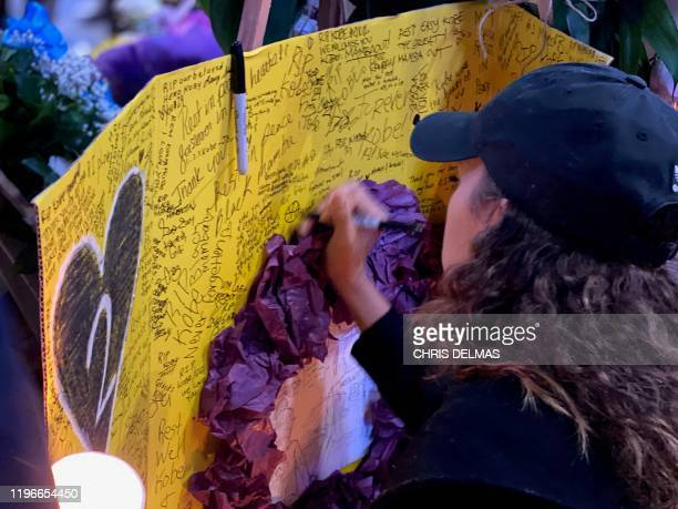 A woman writes words at a makeshift memorial for late basketball legend Kobe Bryant at the Staples center in Los Angeles on January 26 a few hours...