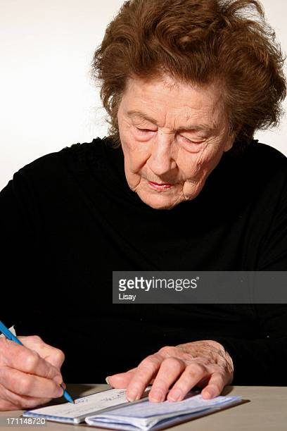 woman writing a check - grandma invoice stock pictures, royalty-free photos & images