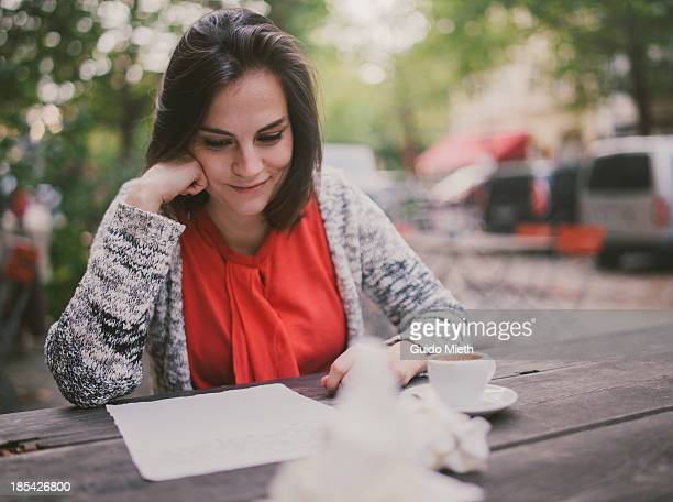 Woman writing a letter in cafe