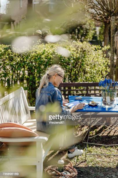 Woman writing a letter on garden bench