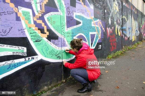 woman writing a message of peace on the belfast wall separating catholics from protestants during day of autumn - belfast stock pictures, royalty-free photos & images