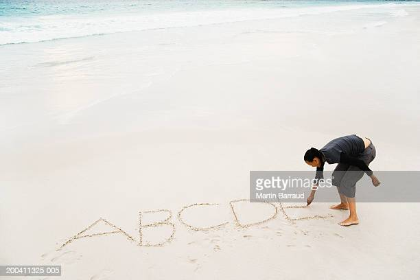 Woman writing alphabet in sand on beach, elevated view
