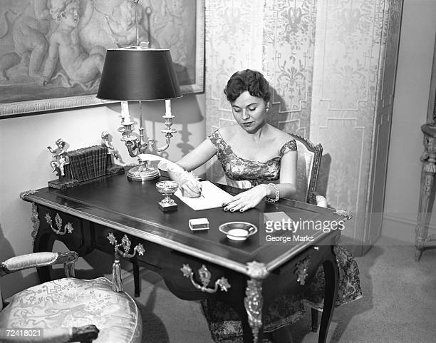 woman writing at desk with quill pen, (b&w), elevated view - quill pen stock photos and pictures