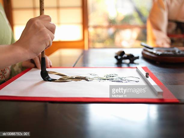 Woman writing calligraphy, close up of hand