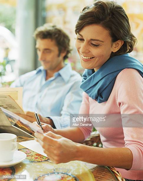 Woman writing card in cafe, smiling, man in background