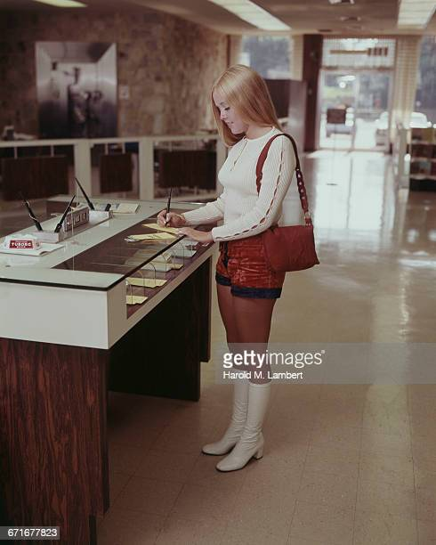 woman writing check in bank  - 1971 stock pictures, royalty-free photos & images