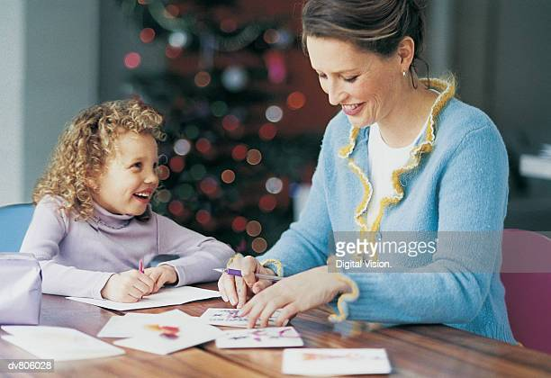 Woman Writing Christmas Cards with Daughter Helping her