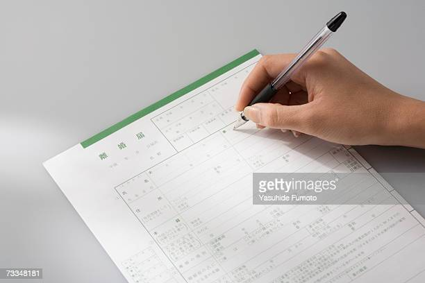 Woman writing divorce application, close-up on hand