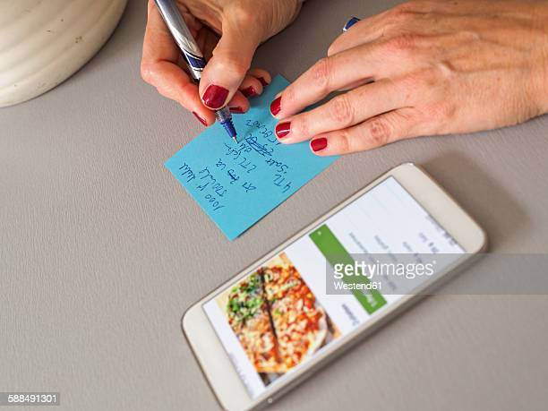 Woman writing down recipe on a note