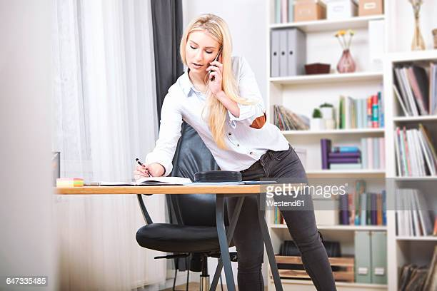 woman writing down something at desk in her home office while telephoning - beautiful women bent over stock photos and pictures