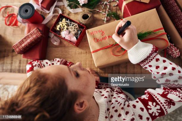 Woman writing greetings on Christmas presents