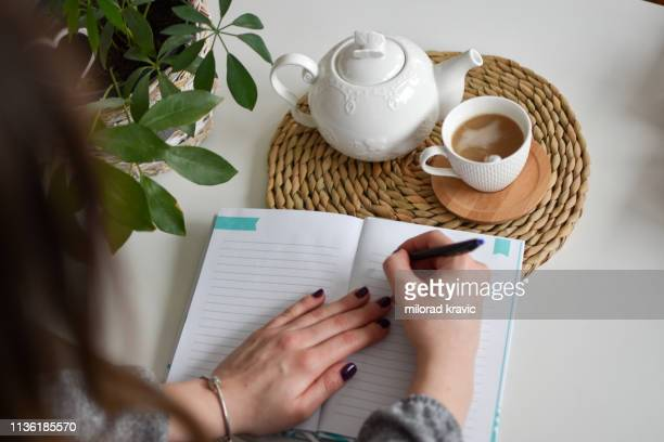 woman writing her notebook - diary stock pictures, royalty-free photos & images