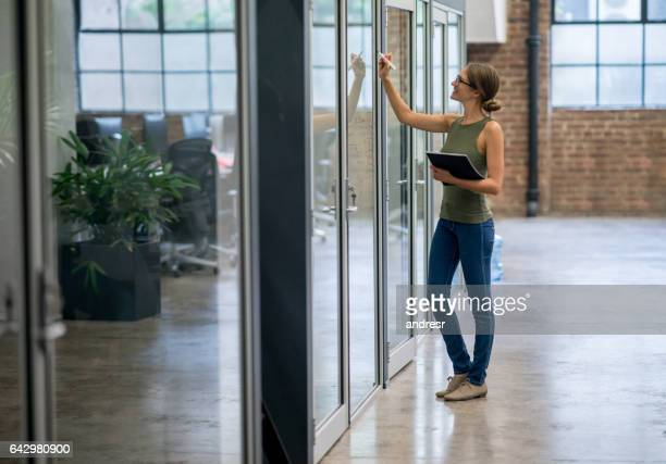 Woman writing ideas on a board at the office