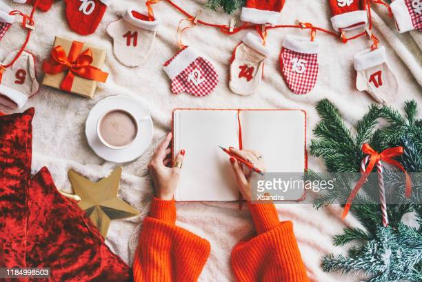 woman writing in a blank notebook - christmas concept flat lay - list stock pictures, royalty-free photos & images