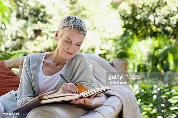 woman writing in a journal - diary stock pictures, royalty-free photos & images