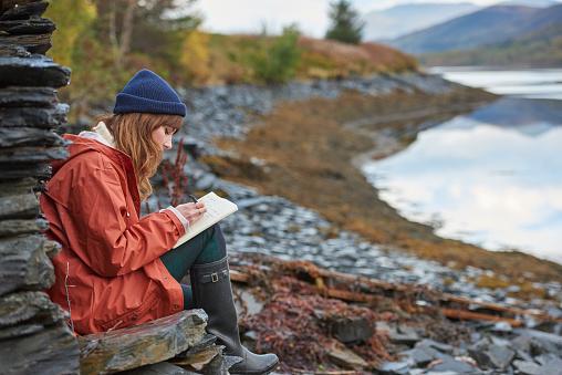 Woman writing in a journal - gettyimageskorea