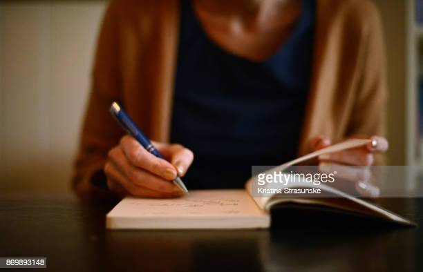 woman writing in a note book - authors stockfoto's en -beelden