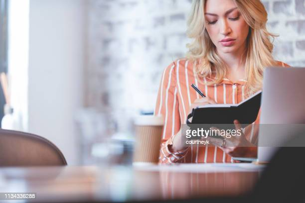 woman writing in a note pad or filofax. - list stock pictures, royalty-free photos & images