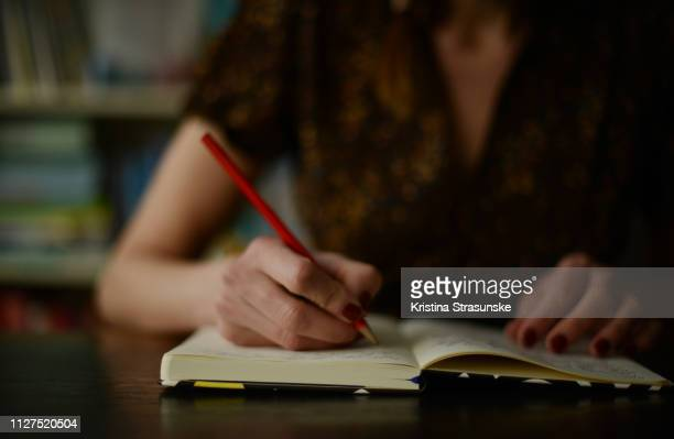 woman writing in a note pad - kristina strasunske stock photos and pictures