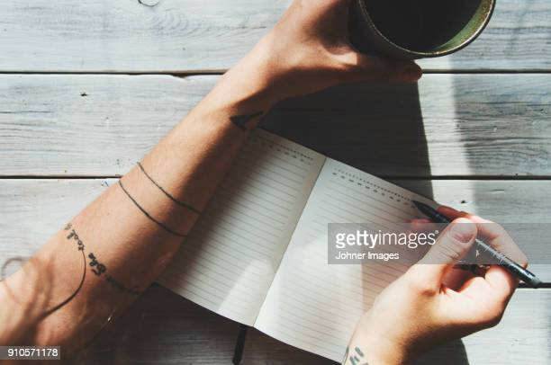 woman writing in a notebok - human arm stock pictures, royalty-free photos & images