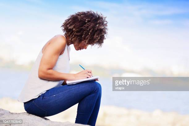woman writing in a notebook outdoors - diary stock pictures, royalty-free photos & images