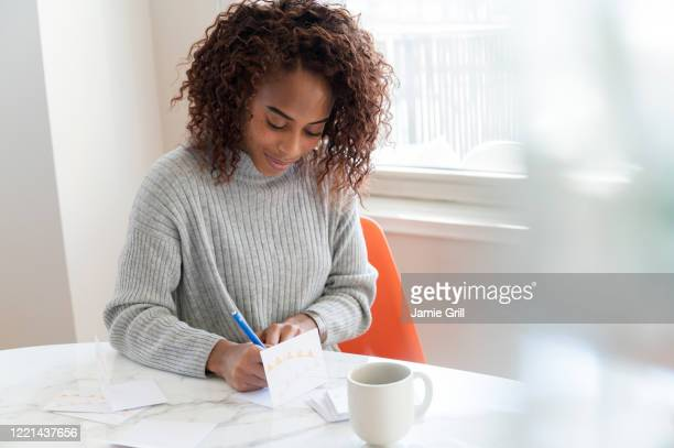 woman writing in card at table - greeting card stock pictures, royalty-free photos & images