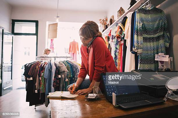 Woman writing in diary while talking on smart phone at store