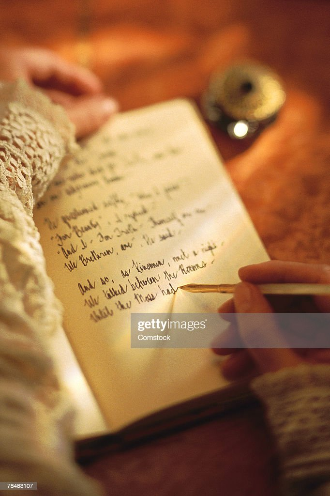 Woman writing in diary with ink pen : Stock Photo