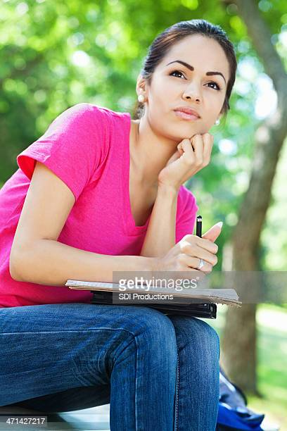 Woman writing in journal at park