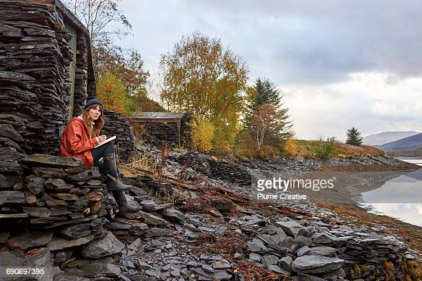Woman writing in journal by Scottish loch