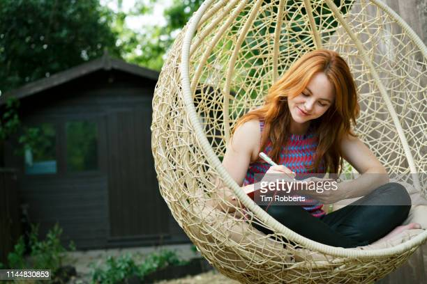 woman writing in journal on swing seat outside - writing stock pictures, royalty-free photos & images