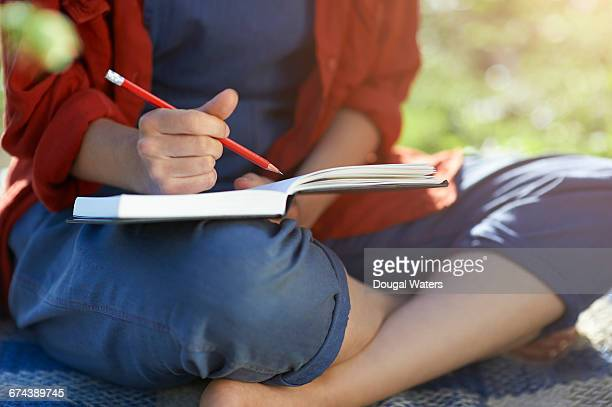 Woman writing in note book.
