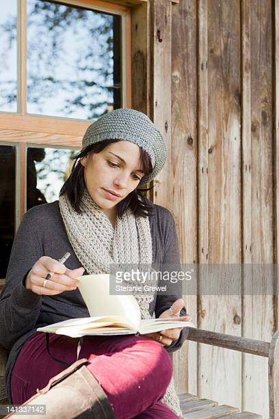 Woman writing in notebook on porch