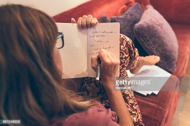 woman writing in notebook - authors imagens e fotografias de stock
