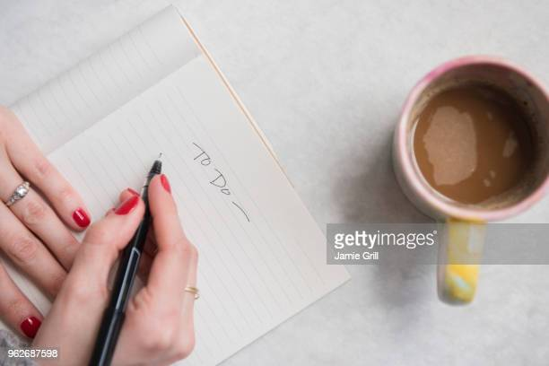 woman writing in notepad - list stock pictures, royalty-free photos & images