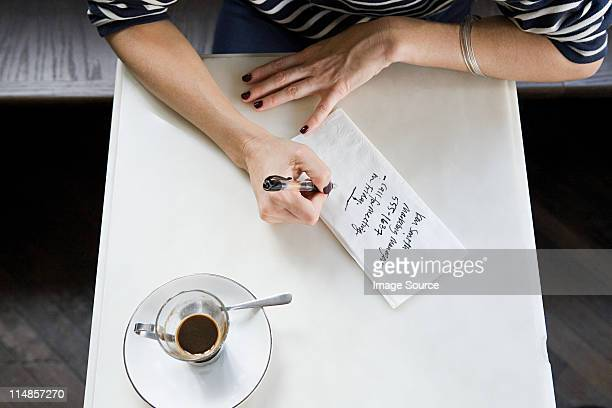 Woman writing note on napkin