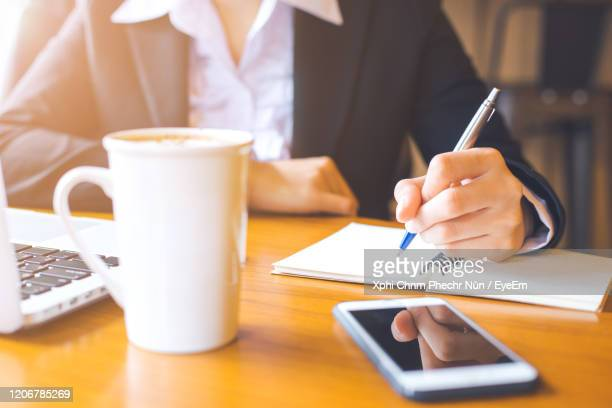 a woman writing on a notepad - journalist stock pictures, royalty-free photos & images