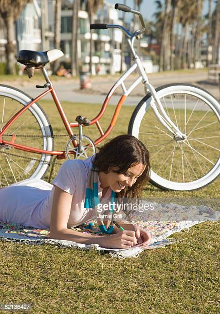 Woman writing on blanket in grass